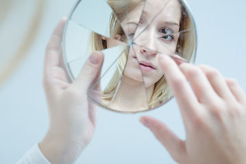girl looking at broken mirror