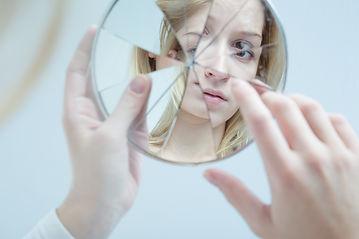 girl looking at broken mirror