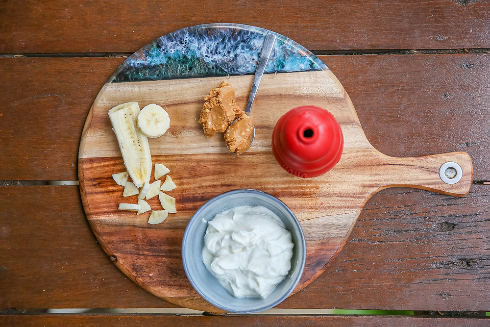 A kong on a platter with the ingredients for its stuffing - banana, peanut butter and greek yoghurt