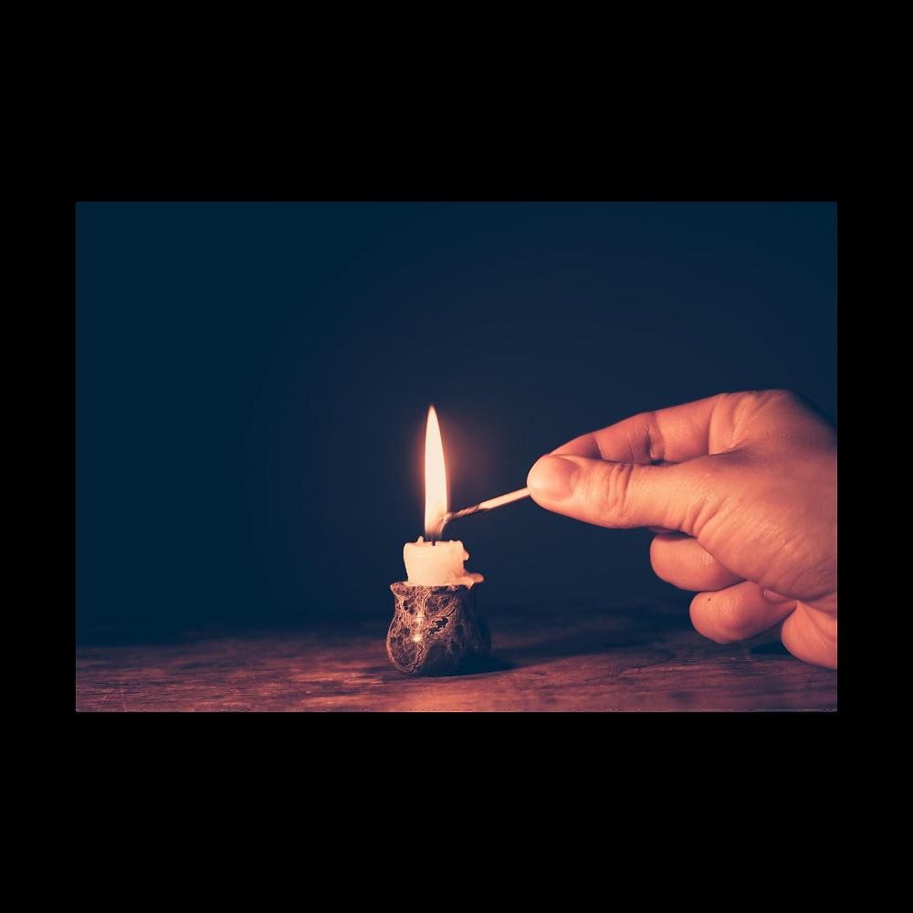 Uma pequena vela sendo acesa na escuridão