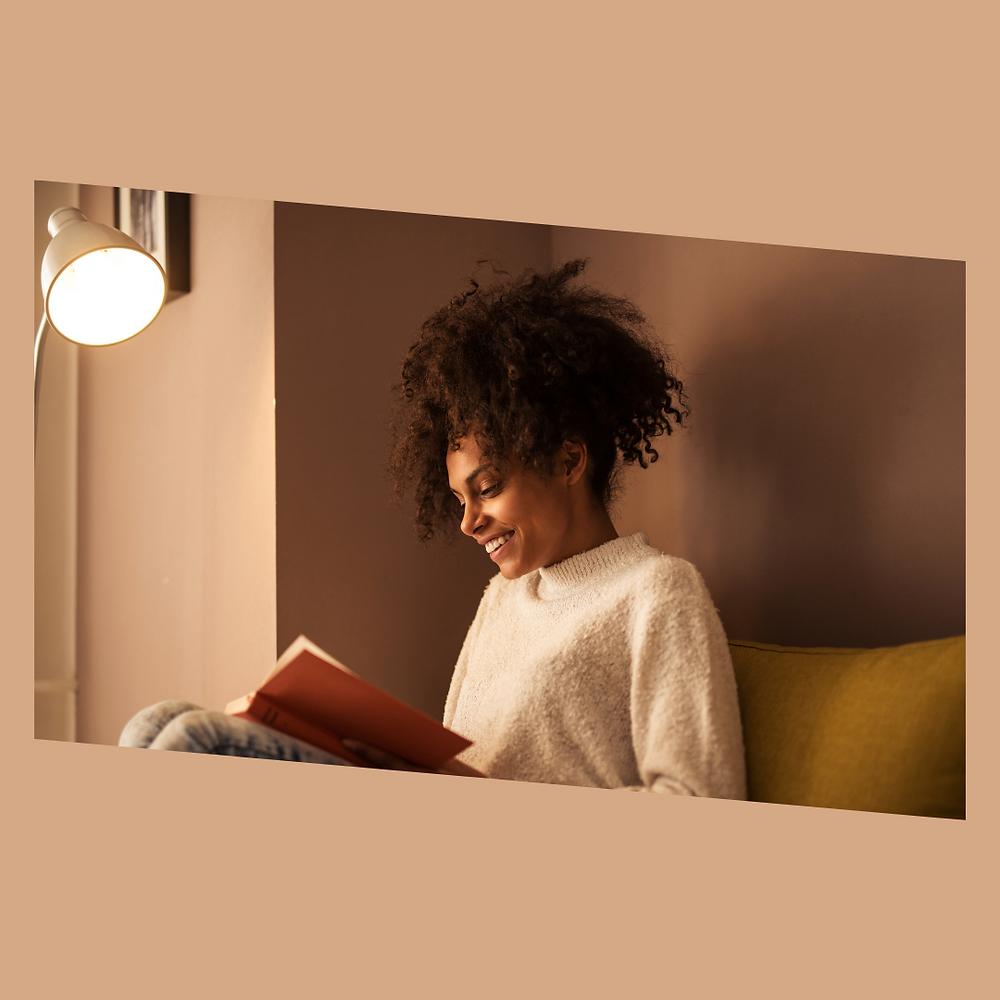 Uma mulher sentada no sofá, com um livro na mão e sorrindo dando a impressão de estar contente com sua leitura.