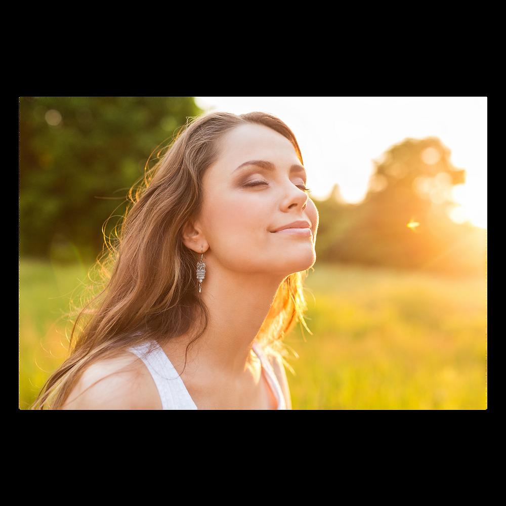 Imagem em que uma mulher sorri de olhos fechados sentindo o calor do amanhecer.