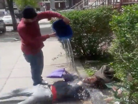 Homeless man sleeping in front of home gets water dumped on him while sleeping.