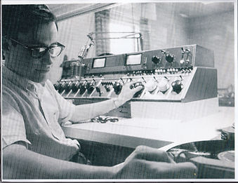 A disc jockey working in the booth getting a record ready in the Union Building in the 1960's
