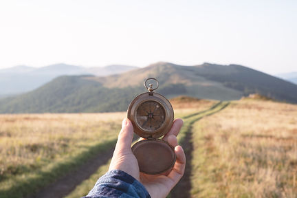 Man with old metal compass in hand on mo
