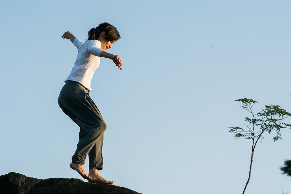 Mulher saltando sobre uma pedra