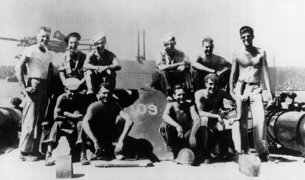 Kennedy (right) with crew at South Pacific Naval Base during World War II / Photo by National Archive / Newsmakers via Getty Images)