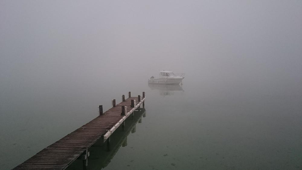 Boat leaving dock in fog