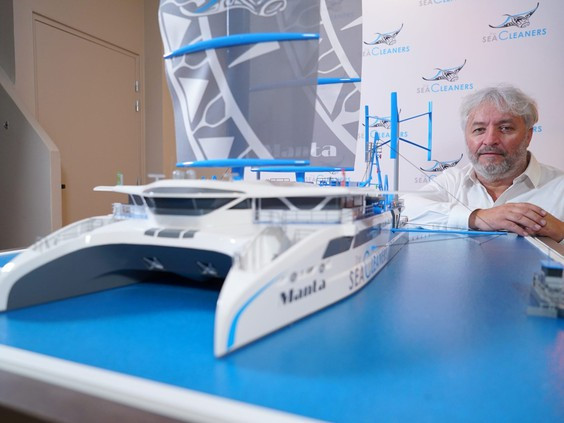 'The SeaCleaners' NGO, Yvan Bourgnon, poses next to a model of the 'Manta,' a giant sailing boat which will collect and recycle the oceans' floating plastic
