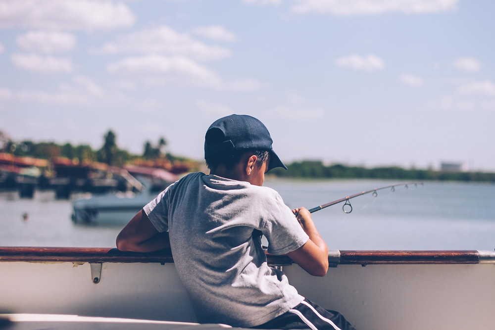 Child on boat with fishing rod
