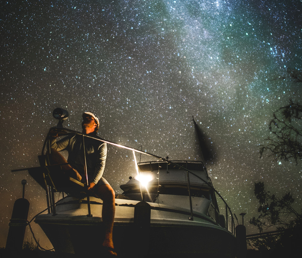 Man sitting at bow of boat at night