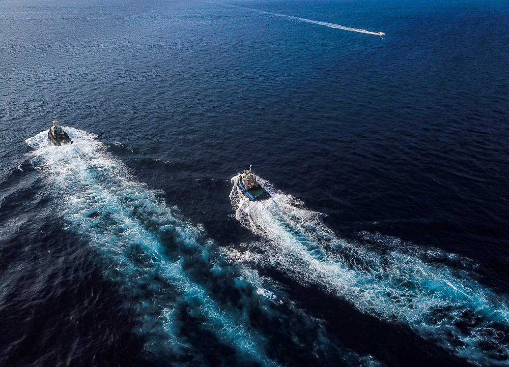 Two boats creating wakes close together
