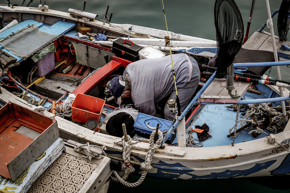 Man cleaning old fishing boat