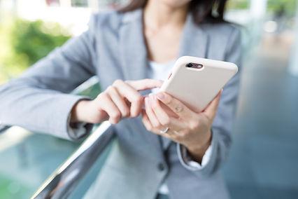 businesswoman-using-cellphone-K8MT8S3.jp