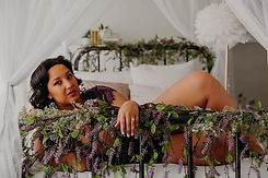 Beautiful woman laying on her side on an iron bed wrapped in purple flowers.