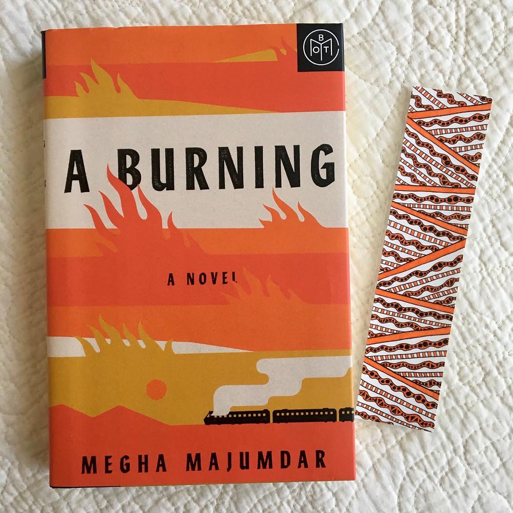 A Burning by Megha Majumdar next to an orange doodled bookmark