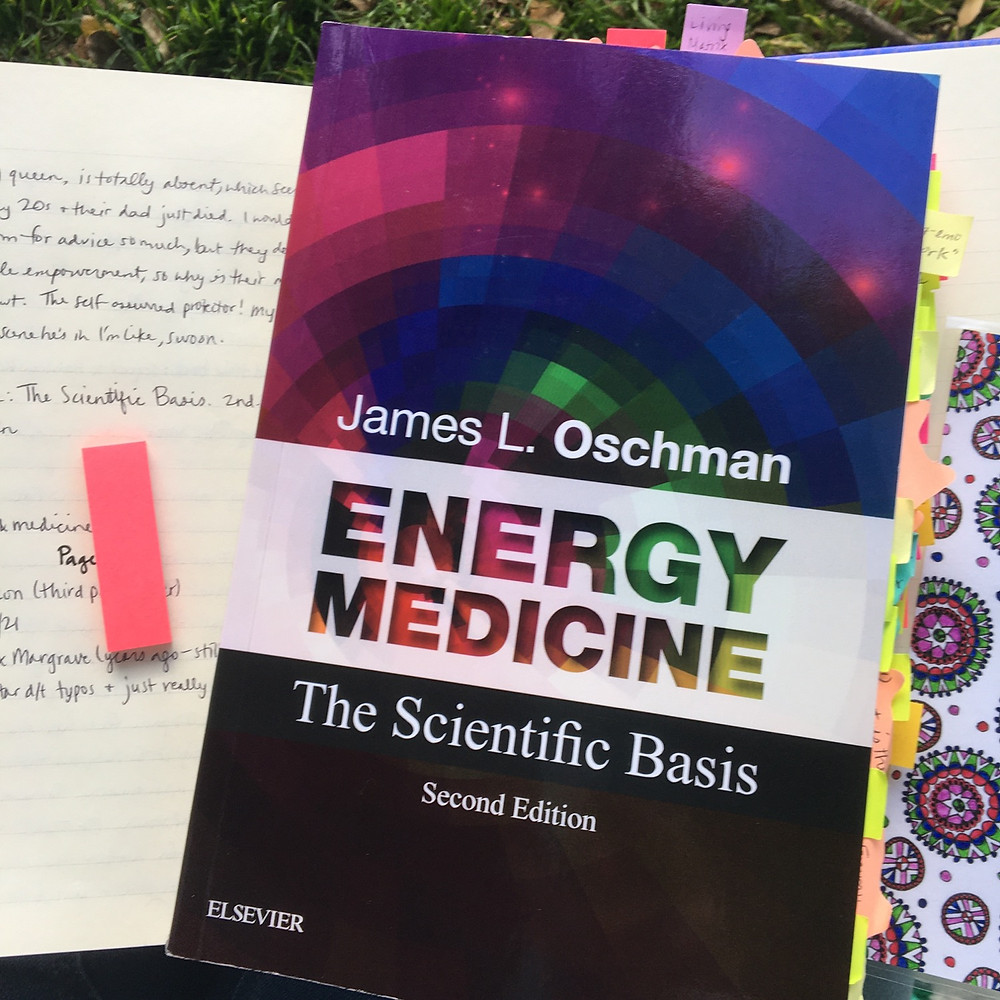Energy Medicine by James L. Oschman with lots of post-its sticking out of it, laying on top of an open journal and a bookmark alongside it
