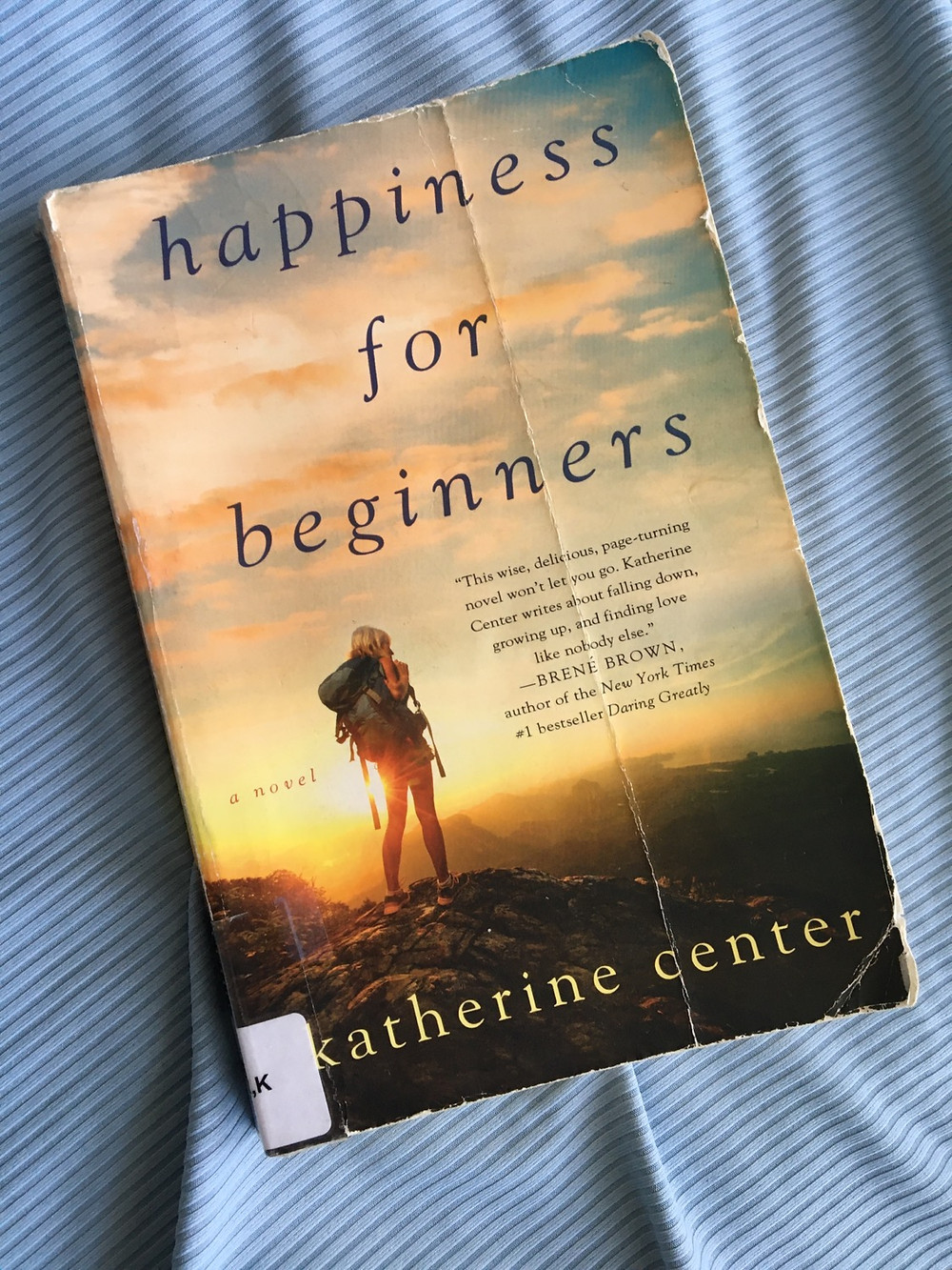 Book photo of Happiness for Beginners by Katherine Center with blue fabric background