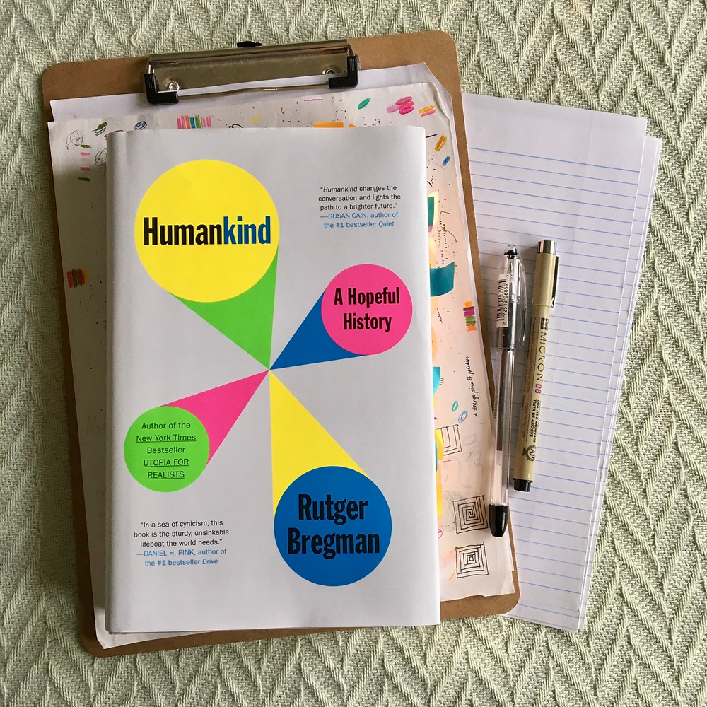 Humankind by Rutger Bregman with clipboard paper and pens