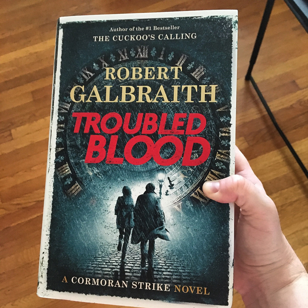 Held in right hand, the book Troubled Blood by Robert Galbraith with wood floor background