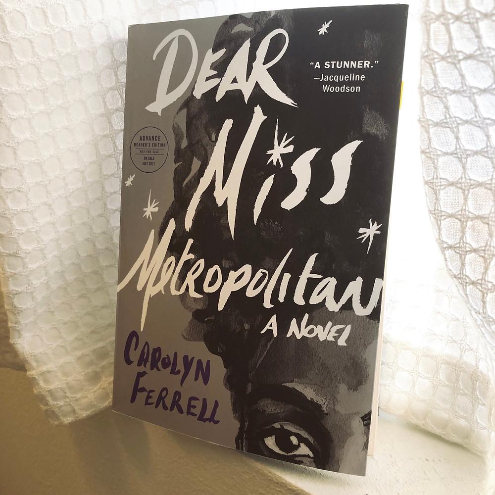 Dear Miss Metropolitan by Carolyn Ferrell sitting on windowsill with white textured curtain background