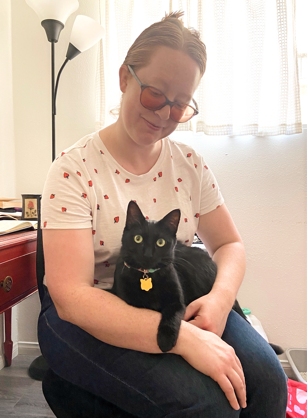 A black cat sits on Allie's lap with one paw over her arm, while Allie looks down on her smiling