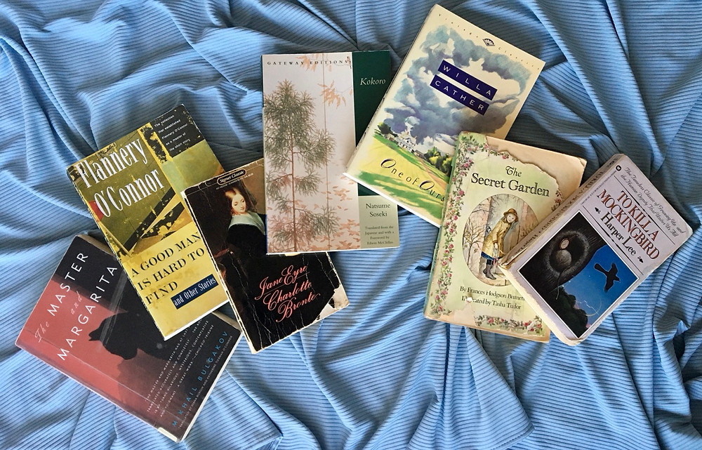 Seven paperback books are laid out over a blue cloth. The titles include Master & Margarita, A Good Man is Hard to Find, Jane Eyre, Kokoro, One of Ours, The Secret Garden, and To Kill a Mockingbird.