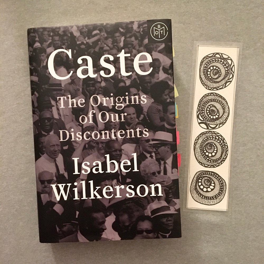 Caste by Isabel Wilkerson with hand drawn bookmark on heather gray background