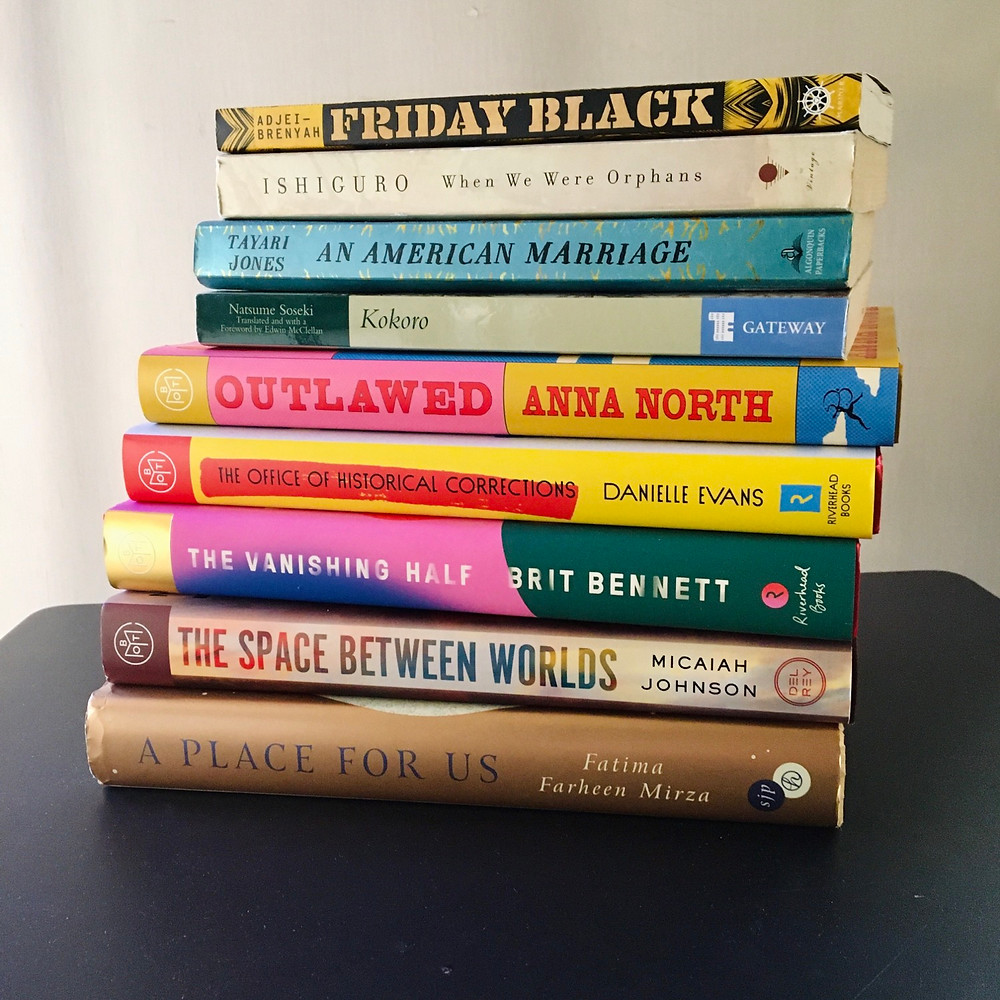 A pile of books: Friday Black by Nana Kwame Adjei-Brenyah When We Were Orphans by Kazuo Ishiguro An American Marriage by Tayari Jones Kokoro by Natsume Soseki Outlawed by Anna North The Office of Historical Corrections by Danielle Evans The Vanishing Half by Brit Bennett The Space Between Worlds by Micaiah Johnson A Place for Us by Fatima Farheen Mirza