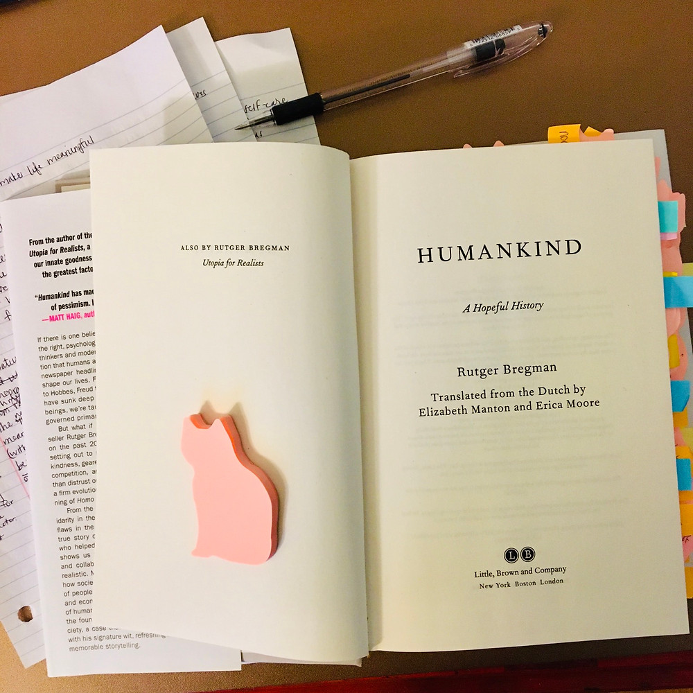 Humankind a hopeful history open to the title page with cat shape lined paper and pen