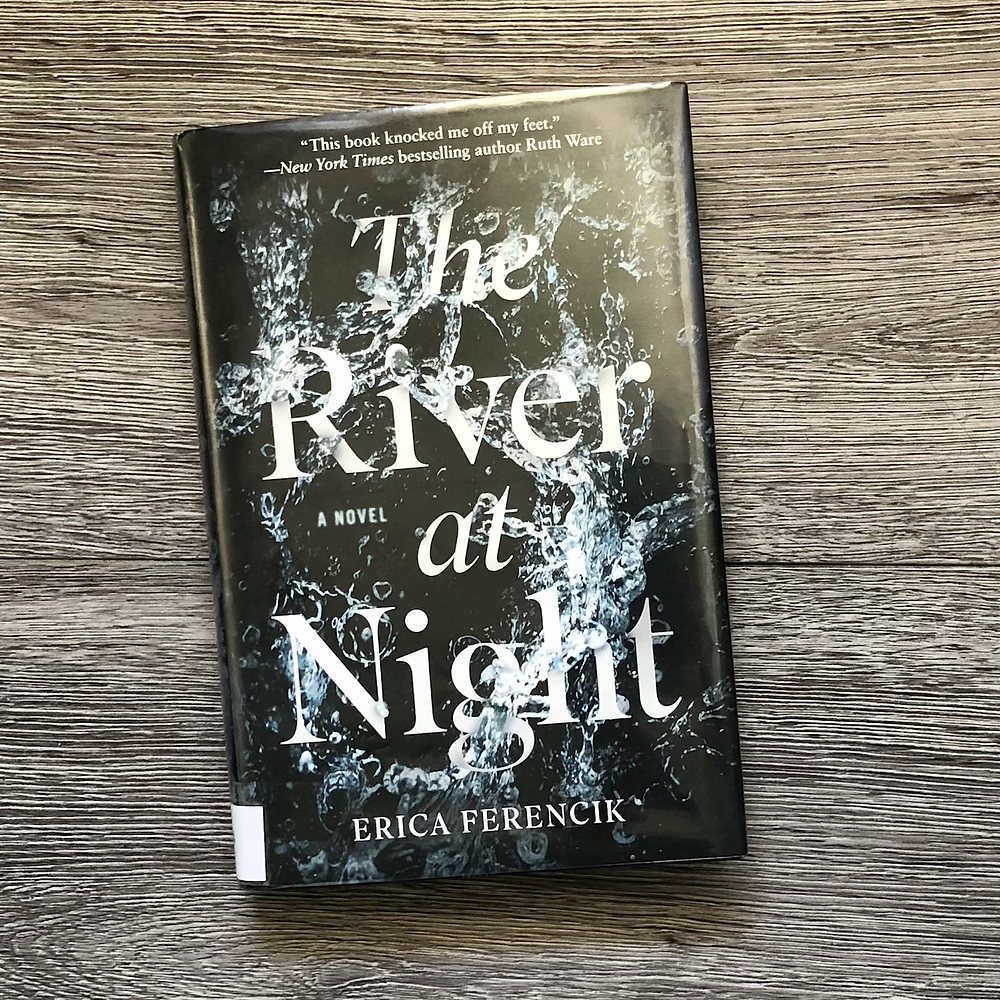 The book The River At Night by Erica Ferencik with gray wood background