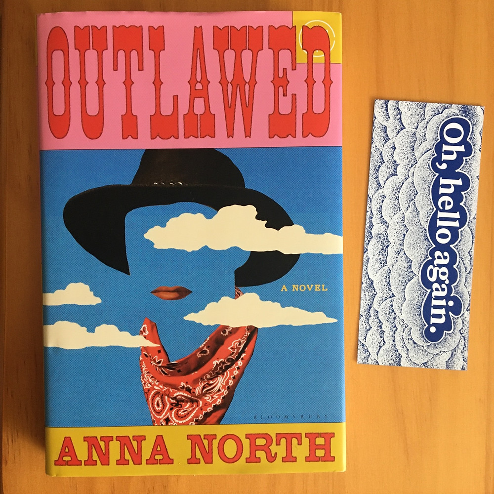 """Outlawed by Anna North with bookmark beside it with the words """"Oh, hello again"""" and a cloud design"""
