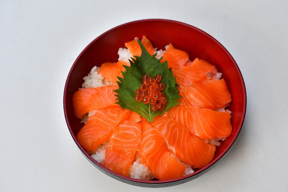 Bowl of rice and salmon topped with garnish of roe
