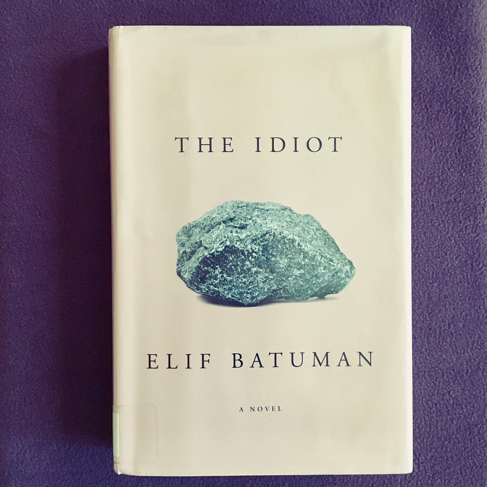 The book The Idiot by Elif Batuman with a violet background
