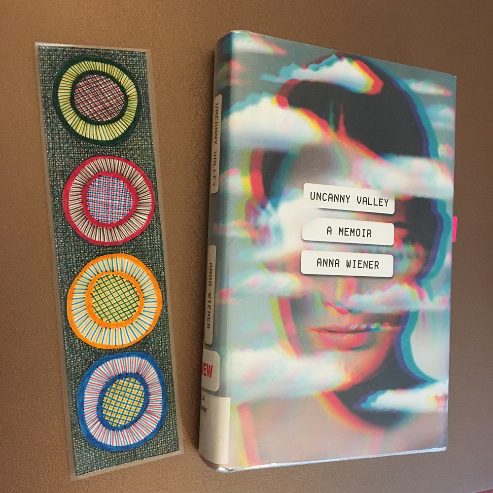 Bookmark with green, red, yellow, and blue circles next to book Uncanny Valley by Anna Wiener