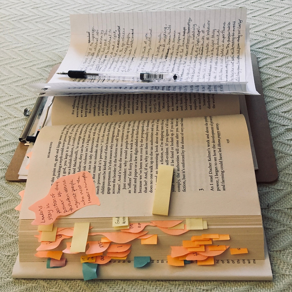 Open book with post-its between the pages, a cat-shaped post-it, a pen and writing paper on top