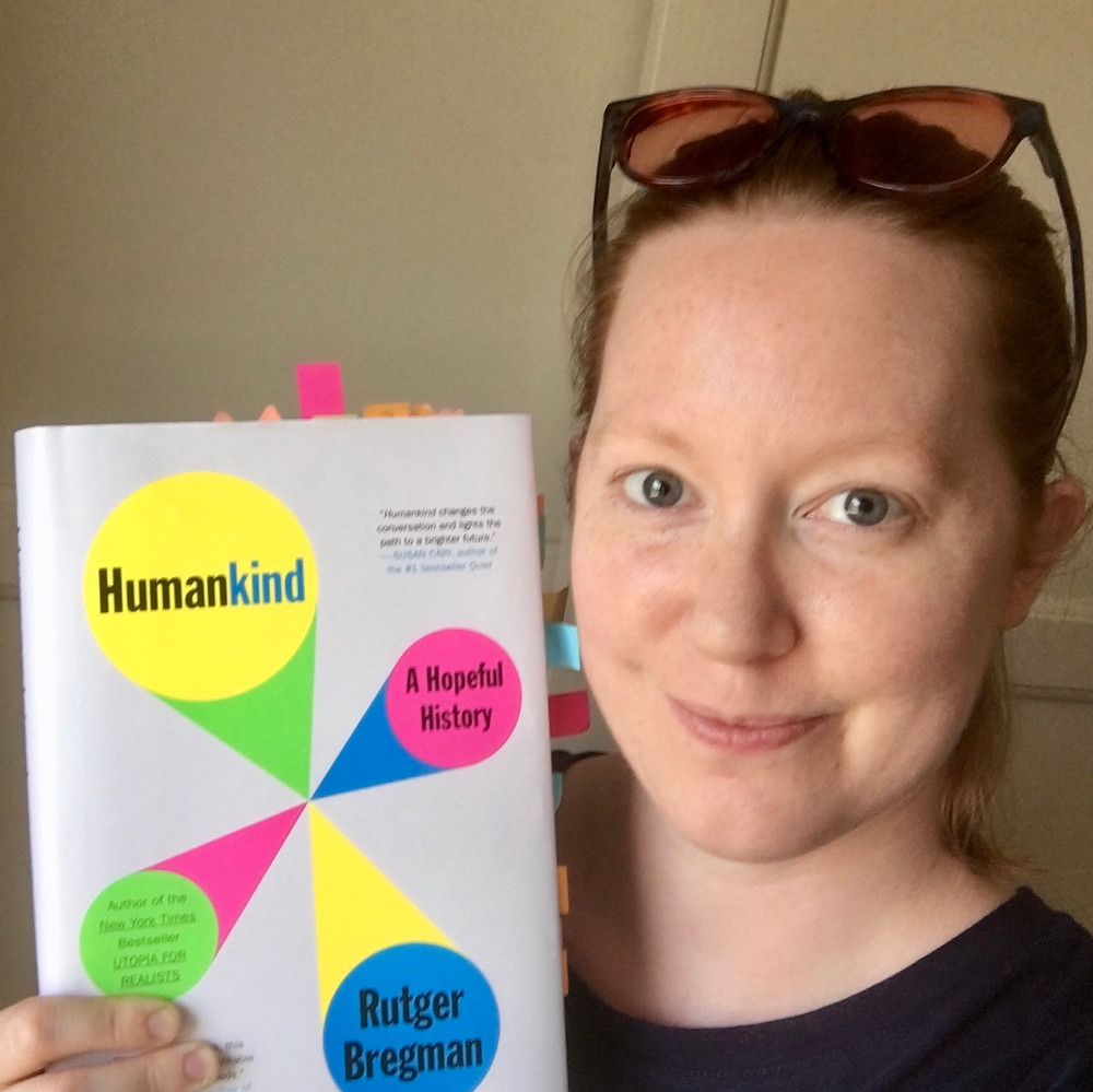 Blogger Allie Phillips smiling and holding a copy of Humankind by Rutger Bregman