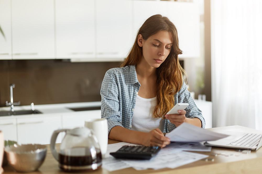 Mujer realizando cuentas debido a que pago el 3%a pensión para los periodos de abril y mayo y ahora debe completar el aporte faltante.