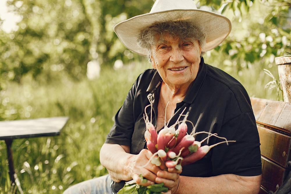 Trabajadora del agro sonriente al saber que puede acceder al piso social y beneficiarse de los servicios que éste ofrece.