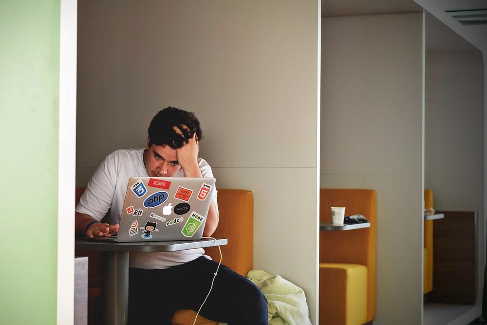 trabajador estresado por continuar trabajando luego de haber finalizado el horario de trabajo, por tener que atender mensajes y llamadas.