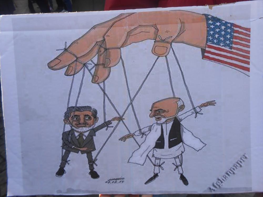 Diese Karikatur zeigt rechts das Staatsoberhaupt und Regierungschef Mohammad Ashraf Ghani und links den Regierungsvorsitzenden Abdullah Abdullah von Afghanistan als Marionetten am Arm der USA.