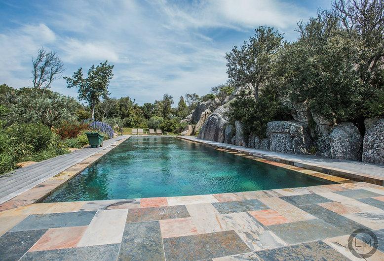 Piscine rectangulaire pierre et bois dans jardin Corse