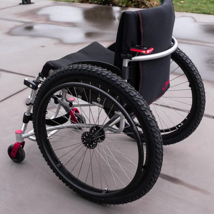 Fullt vinterutrustad rullstol med grova vinterdäck och belysning fram och bak.