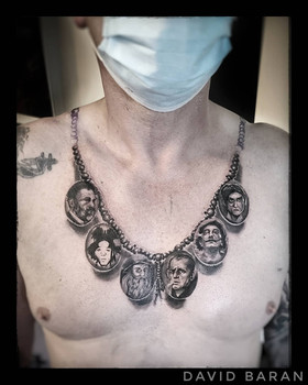 A realistic necklace and pendant tattoo by David Baran