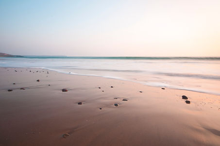 Sandy beach with lapping waves and a blue green pink horizon at the beach