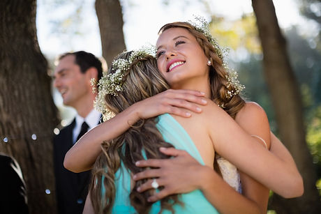 bride-embracing-her-friend-in-park-MDP9W