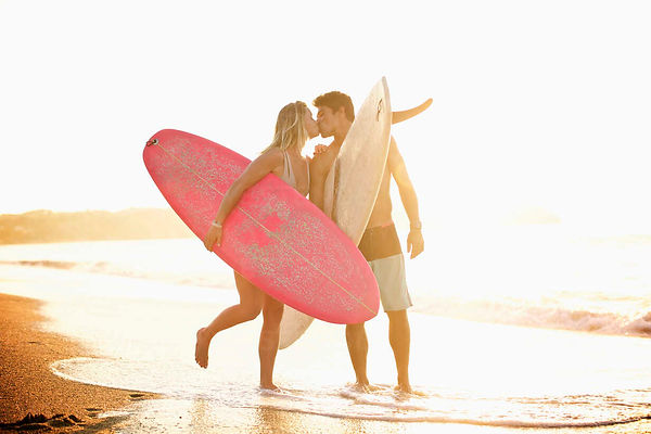 young-affectionate-couple-with-surfboard