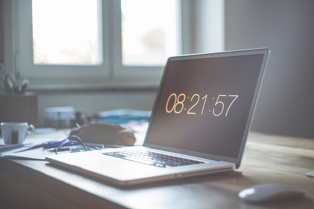 Stock image of laptop on desk displaying time remote work and work from home