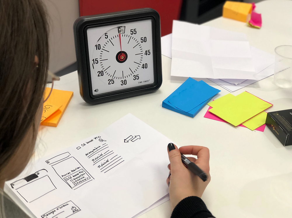 Stock image of woman making notes in notebook, drawing user interface mock-ups of software and website, with timer clock in background