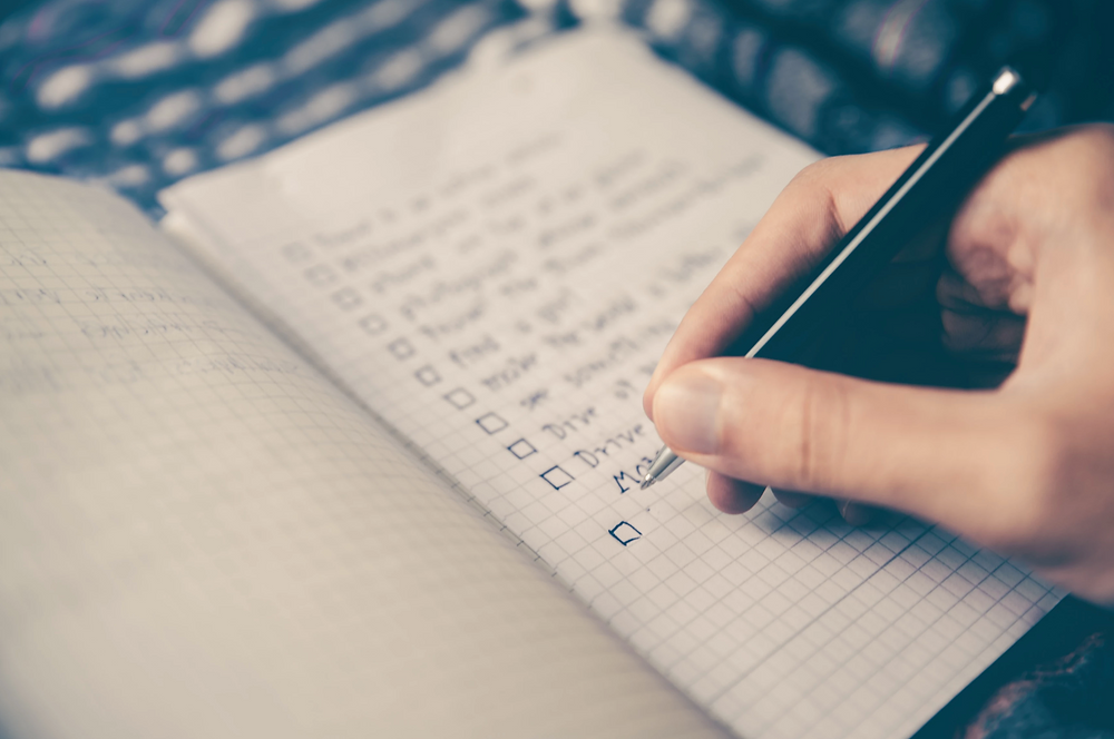Stock image of person writing a list in grid line bullet notebook journal